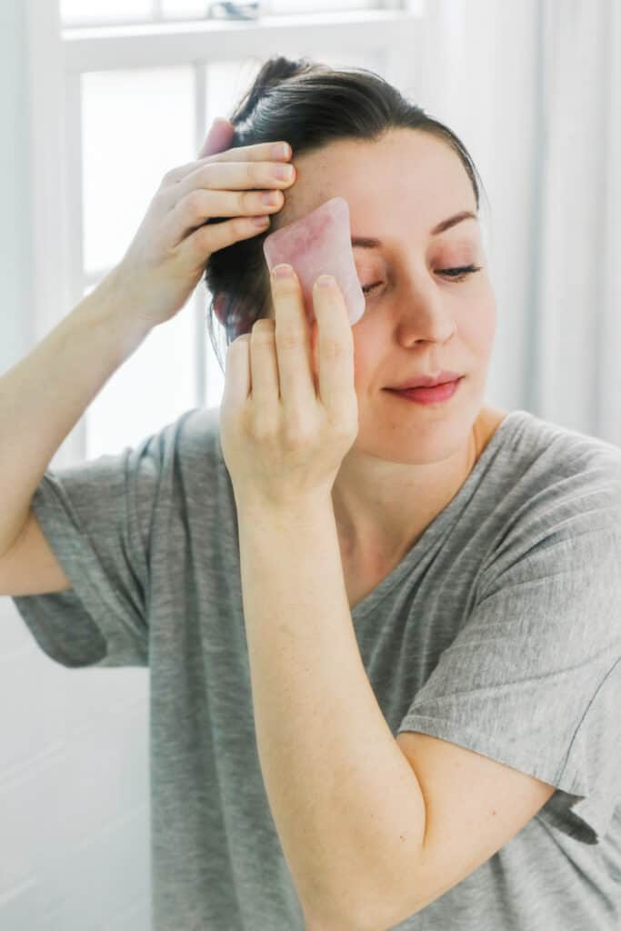 Massaging Forehead with Gua Sha stone